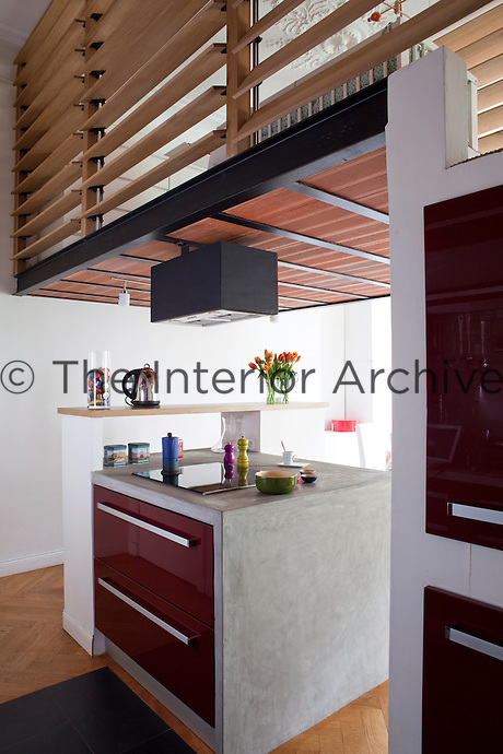 This open plan kitchen has an island in concrete with lacquered burgundy coloured doors and other work surfaces in close proximity, creating a convivial  and practical cooking area