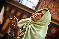 A kashmiri muslim woman prays at the  Dasrgir Saheb shrine in Srinagar. Muslims around the world are attending the holy month of Ramadan, where they observe the devout fast from dawn to dusk.