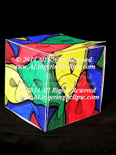 Fish swim in this colorful design created by artist AnnaLise S. Hoopes.  This is a cube, made of folded paper (see edge lift) to illustrate design concepts and wrap around perspectives in drawing using pen, ink, pencil & watercolor paints of yellow, red, blue and green.