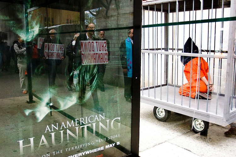 A caged protester is wheeled past a bus stop during a protest in New York City on May 1, 2006 for those tortured and unjustly imprisoned at Guantanamo Bay.
