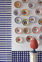 A colourful display of hand-painted ceramic bowls competes with the strong pattern of the blue and white tiles on a kitchen wall