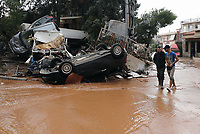 Pictured: Local people inspect a pile of cars in the middle of the road.<br />