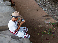 A local Khmer boy and his cell phone at the entrance of Angkor Wat, Cambodia.