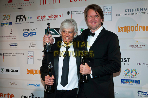 "TARIQ ANWAR & TOM HOOPER - ""The Kings Speach"" (European Editor 2011 + Peoples Choice Award 2011).The 24th European Film Awards 2011 at Tempodrom, Berlin, Germany. .December 3rd, 2011.half length black jacket suit white shirt winner award trophy trophies.CAP/PPG/NK.©Norbert Kesten/People Picture/Capital Pictures"