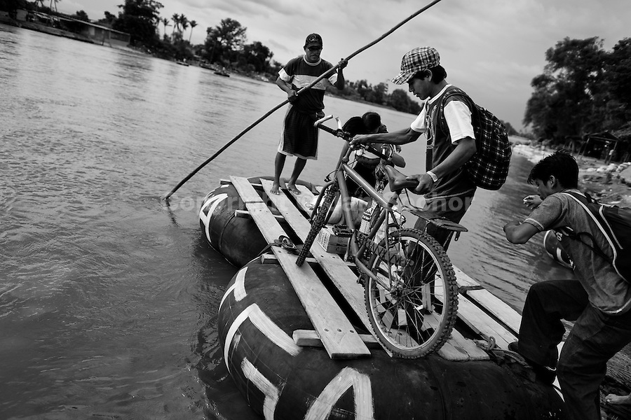 Guatemalan border area workers get on a makeshift inner tube raft to cross the Suchiate river from Tecún Umán, Guatemala, to Mexico, 22 May 2011. Having no migration or commercial controls, the Suchiate river serves as an illegal crossing point between the southern Mexican state of Chiapas and Guatemala. Every day, hundreds of people from both countries, crossing the river on the unstable rafts called ?camaras?, smuggle soft drinks, toilet papers, fruits, vegetables and other supplies. The river crossing is also widely used by the Central America immigrants heading to the north, to the United States, in the search of better life.