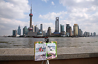 A stand holding souvenir pictures sits on the bund with a view of the Pudong Financial District in Shanghai, China..