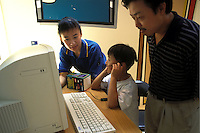 A young boy and his father use a computer equipped with VOIP communications software at an exhibition in Shanghai, China..