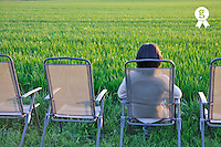 Woman on chair facing green wheat field at sunset (Licence this image exclusively with Getty: http://www.gettyimages.com/detail/81867370 )