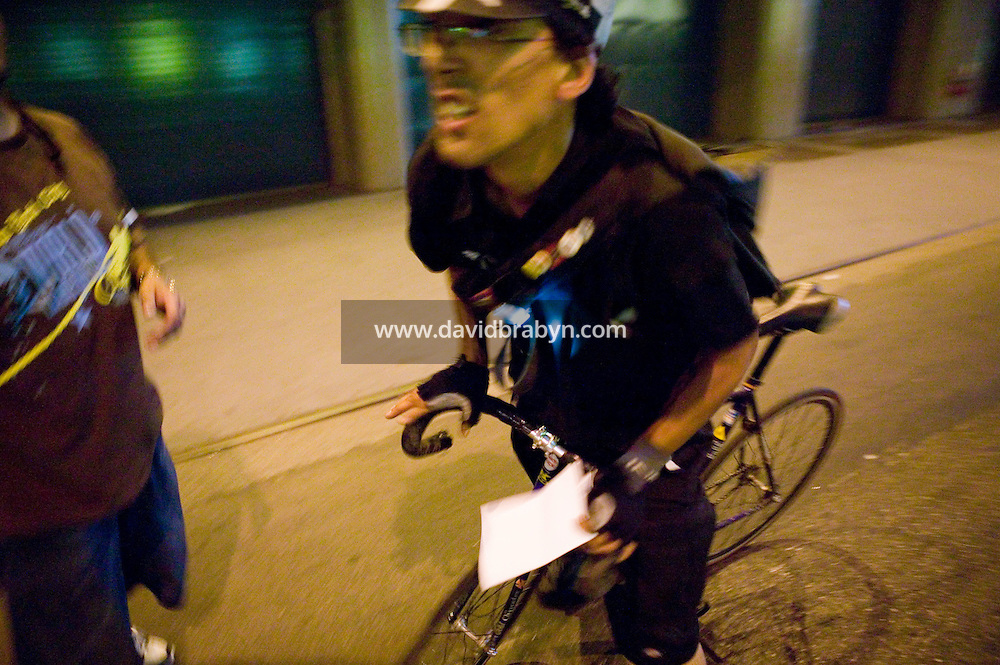 3 July 2005 - New York City, NY, USA - A rider arrives, manifest in hand, at the alleycat checkpoint on 43rd street in New York City, USA, July 3rd 2005. Alleycats are urban cycle races held informally - without notification of the authorities - on open roads and in real traffic, to simulate the messenger's working conditions. Photo Credit: David Brabyn<br />