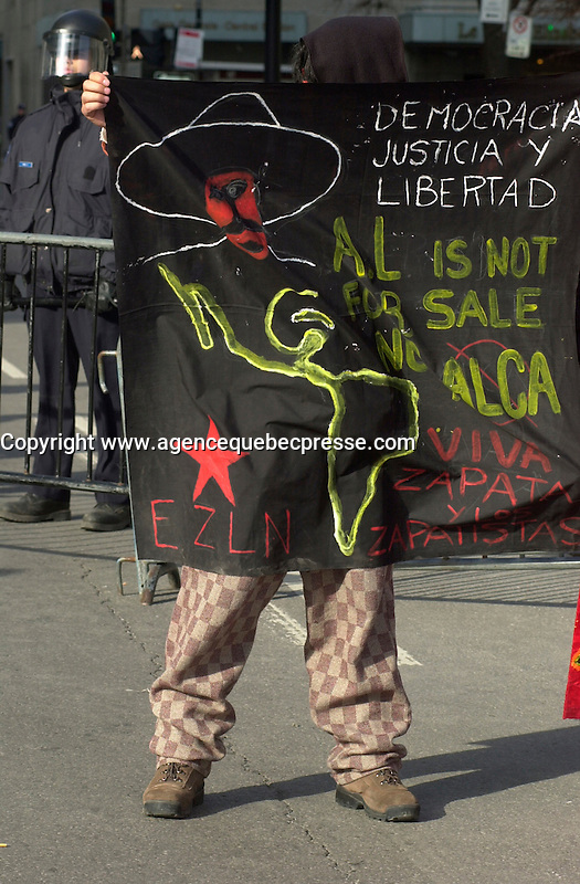 Montreal, April 17, 2001<br /> <br /> One  of demonstrators opposed to the Free Trade Area of the Americas (FTAA) look like he is part of  a banner in spanish for Democracy, Justice and Liberty<br /> near the Police barricades <br /> on April 17, 2001 in downtown Montreal (Quebec, CANADA), near the and the Queen Elizabeth Hotel where the `` Conference of Montreal `` on economy globalization is beeing held until April 19th 2001.<br /> <br /> The  conference feature speakers such as Mexico President Foxx and New York Governor Pataki.<br /> <br /> Photo by Pierre Roussel / <br /> NOTE :  Uncorrected D-1 JPEG saved as Adobe RGB color space.