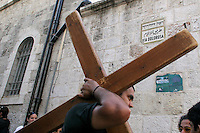 A Christian worshiper carries a cross through the Vial Dolorosa, in the Old City of Jerusalem. Photo by Quique Kierszenbaum