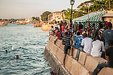 ZANZIBAR,Stone Town, Young Boys sitting on City's Wall next to the Ocean