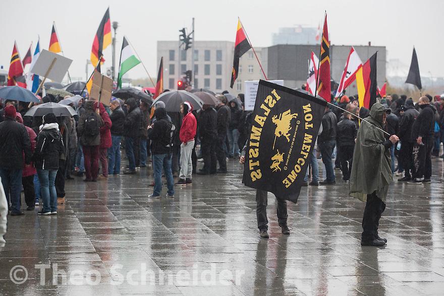 """Ein durchnässter Teilnehmer des rechtsextremen Aufzuges mit islamfeindlicher Flagge der Identitären Bewegung // Rechter Aufmarsch """"Merkel muss Weg!"""" und Gegenproteste in Berlin."""
