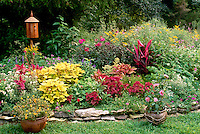 Raised garden bed full of multi-colored  flowers and hand made birdhouse