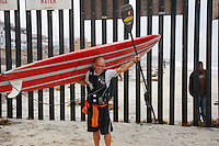 "Tom Jones carries his 14ft paddleboard away from the US Mexico border at Border Field State Park, the south-western most corner of the contiguous United States, Friday, November 9, 2007.  Jones became the first person to paddle the entire 1250-mile coast of the California on a paddleboard when his three and a half month long journey ended at the border fence in southern San Diego.  The expedition, called ""California Paddle 2007"" was designed to draw attention to the problem of plastic pollution in the world?s oceans and its detrimental effect on marine life. (Photo Ronan Gray)"