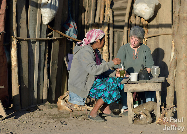 A Wichi indigenous woman, Griselda Arias (left) shares tea with Sister Norma Chiappe, at Arias' home in Lote 75, an indigenous neighborhood of Embarcacion, Argentina. The Wichi in this area, largely traditional hunters and gatherers, have struggled for decades to recover land that has been systematically stolen from them by cattleraisers and large agricultural plantations. Chiappe is a member of the Franciscan Missionaries of Mary who lives in Lote 75.