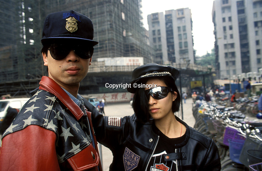 A young couple pose in the street in Guangzhou wearing expensive American-style leather fashions.