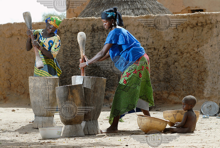 "Nana Badama (left) and Hinda Salha (right) grind millet to make an edible ""kalebash"" paste in Dan Saga village."