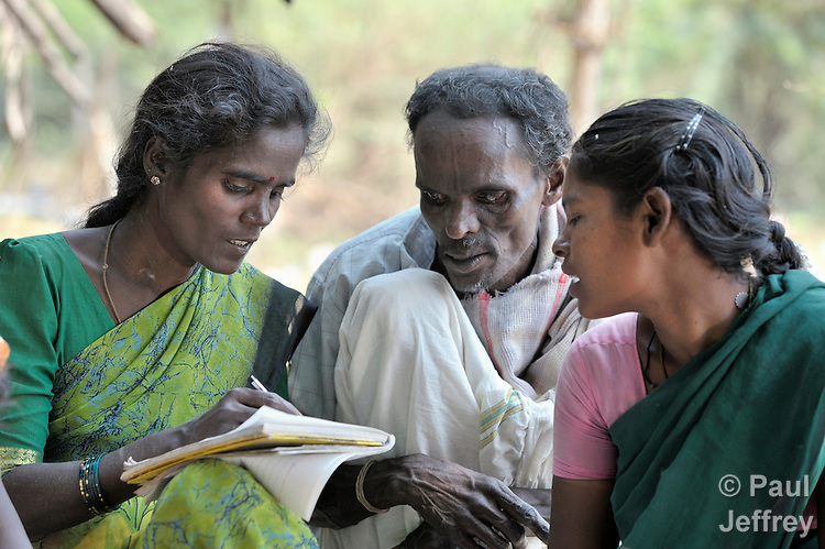 Kuttiamma (left) gets help from her husband Chandaran and another woman as she writes during a women's literacy class in Nandambakkam, a tribal village in the southern India state of Tamil Nadu.