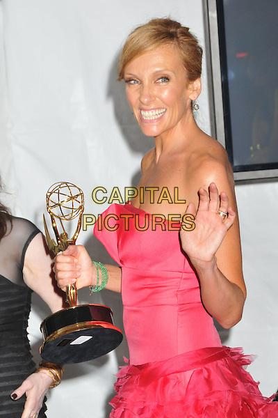 TONI COLLETTE .Attending the 61st Annual Primetime Emmy Awards held at NOKIA Theatre L.A. LIVE, Los Angeles, California, USA, .20th September 2009..pressroom press room emmys half length trophy award strapless pink dress side hand waving hair up smiling green stone bracelet .CAP/ADM/BP.©Byron Purvis/Admedia/Capital Pictures