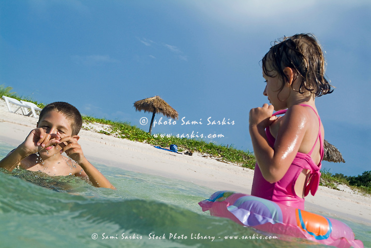Boy and girl swimming in the tropical water at Cayo Jutias, Cuba.