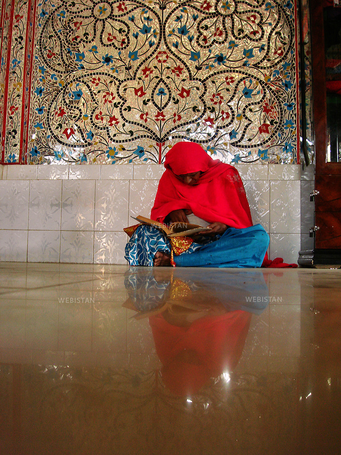 SEHWAN SHARIF, PAKISTAN - JANUARY, 2007:.Portrait of a woman reading the Quran inside the shrine of Bodla Bahhar, one of the main disciples of Lal Shahbaz Qalandar, a 13th century Sufi Master worshiped alike by Hindus and Muslims. Born as Seyed Shah Hussain (Usman) Marandi, he later on titled as Lal (red) Shahbaz ( Falcon) Qalandar (as he belonged to Qalandria order of sufism).