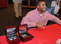 Red Sox Minor League outfielder and former University of South Carolina Gamecock Jackie Bradley Jr. signs autographs next to a display of his college championship rings at the Greenville Drive Hot Stove Event on January 23, 2012, in Greenville, South Carolina. Bradley was a top pick of the Boston Red Sox in the 2011 draft and played briefly in the Sox' Minor League system late in the 2011 season. (Tom Priddy/Four Seam Images)