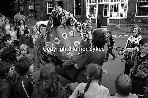 Minehead Hobby Horse Somerset. UK.  &quot;Booting&quot; ceremony oin the centre of town on last evening. A boy, a  young person is held out in front of the Hobby Horse and struck 10 times by the bow of the Hobby Horse.<br />