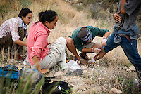 No More Deaths volunteers Jake Olzen (cq), Lucy Zhang (cq, in pink), and Heather Vega (cq) tend to a knee injury on a migrant after an encounter during a water drop patrol near Apache Pass outside Arivaca, Arizona from July 23, 2009. No More Deaths help migrants suffering from dehydration, falls, sprained ankles, blisters, and other hazards commonly occurring from exposure in the desert...PHOTOS/ MATT NAGER