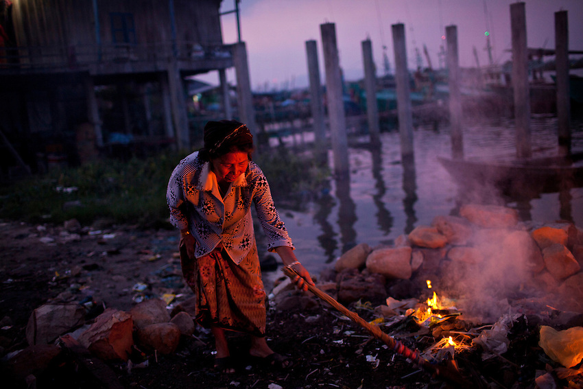 A Cham Muslim woman sweeps debris into a fire at a village on the banks of the Kampong Bay estuary in Kampot province, Cambodia, March 10, 2012.
