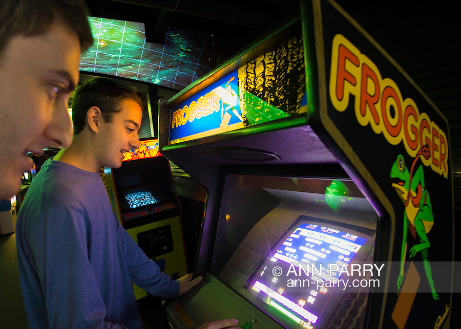 Garden City, New York, USA. December 12, 2015. SETH ROSEN, 15, at right, from Roslyn, NY, and his cousin JACOB ROSEN, 21, from Miami, FLA, play FROGGER, a 1981 Sega Gremlin game, during Opening Day of Arcade Age exhibit, where visitors experience playing authentic classic games in arcade set up at Cradle of Aviation Museum in Long Island. Admission includes unlimited free pay-to-play of video arcade games, and games history is displayed outside arcade area. Exhibit runs from Dec. 12, 2015 through April 3, 2016.
