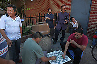 (171015RREI5508) La Esquina where Latinos have gathered for decades at the corner of Mt. Pleasant St. and Kenyon St. NW. to play chekers (damas). Jorge (lgreen shirt)), Jose center, hat), David (Curunco) front of door. Washington DC Oct. 15 ,2017 . ©  Rick Reinhard  2017     email   rick@rickreinhard.com