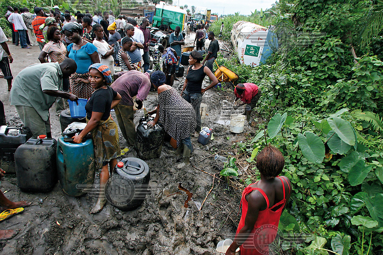 People fill containers with fuel stolen from an overturned tanker on the Warri - Port Harcourt Road.