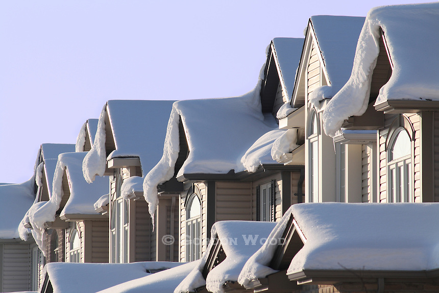 Suburban Houses in Winter with Heavy Snow on Roofs