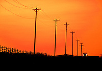 The distant headlights of a lone aproaching car as it travels over a country road, past an expanse of telephone lines and poles in silhouette under a sunset sky