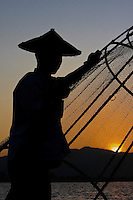 Myanmar, Burma.  Fisherman with Fishnet at Sundown, Inle Lake, Shan State.