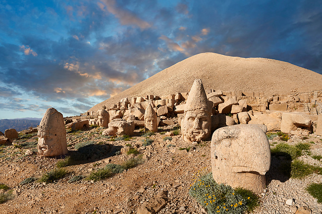 Statue heads at sunset, from froint, of an eagle, Herakles & Apollo, & Zeus (left), in front of the stone pyramid  62 BC Royal Tomb of King Antiochus I Theos of Commagene, west Terrace, Mount Nemrut or Nemrud Dagi summit, near Adıyaman, Turkey