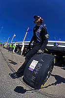 A crewman for Jimmie Johnson (#48) rolls a tire through the garage area.