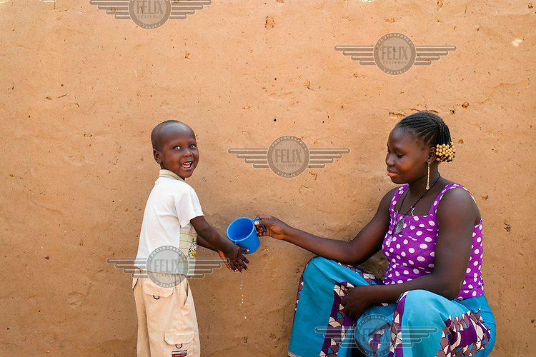 Juliette Ilboudo pours water for her son Herman to wash his hands at their home in the informal settlement of Zongo.