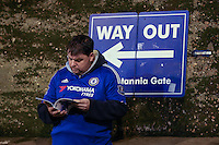 With the speculation over Jose Mourinho's future at Chelsea, a Chelsea fn reads the programme in front of a sign showing the Wy Out of Stamford Bridge ahead of the UEFA Champions League Group match between Chelsea and Dynamo Kyiv at Stamford Bridge, London, England on 4 November 2015. Photo by David Horn.