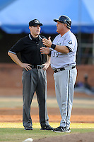 Kannapolis Intimidators manager Tommy Thompson #39 discusses a play with First Base Umpire Ryan Wills during a game against the Asheville Tourists at McCormick Field on May 9, 2013 in Asheville, North Carolina. The Intimidators won the game 13-12. (Tony Farlow/Four Seam Images).