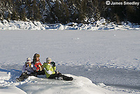 Family drinking hot chocolate outside on the frozen lake ice