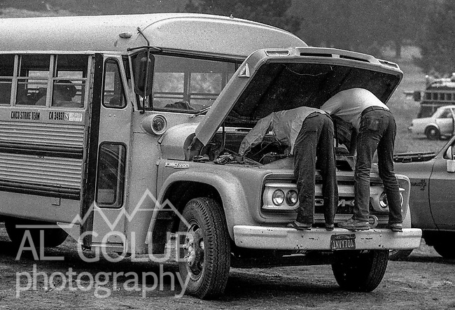 September 2, 1987 Buck Meadows, California – Stanislaus Complex Fire -- Drivers work on crew bus in fire camp in Kassabaum Meadow. The Stanislaus Complex Fire consumed 28 structures and 145,980 acres.  One US Forest Service firefighter, David Ross Erickson, died from a tree-felling accident.
