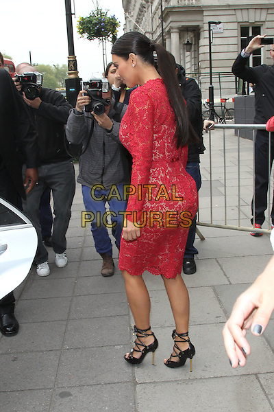 Kim Kardashian  .Leaving her hotel, London, England..March 18th, 2012.full length red pink lace dress strappy black sandals side profile ponytail photographers press paparazzi.CAP/HIL.©John Hillcoat/Capital Pictures.