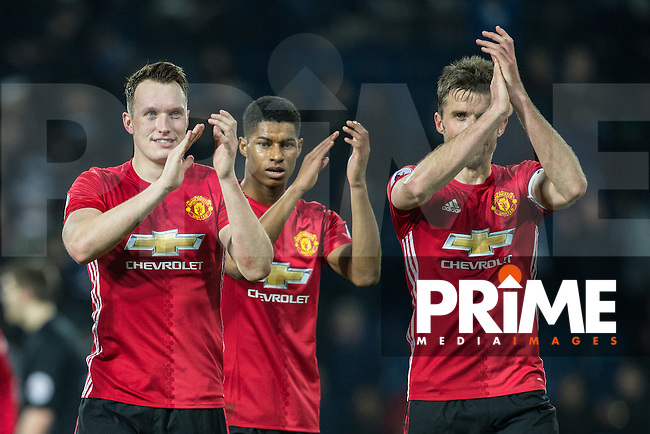 (l-r) Phil Jones, Marcus Rashford & Michael Carrick of Manchester United applaud the support during the EPL - Premier League match between West Bromwich Albion and Manchester United at The Hawthorns, West Bromwich, England on 17 December 2016. Photo by Andy Rowland / PRiME Media Images.