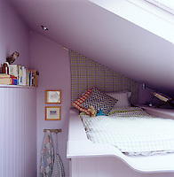 A narrow bed has been built on a raised platform beneath a skylight in the attic