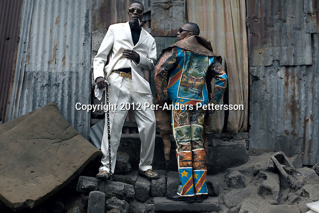 """KINSHASA, DEMOCRATIC REPUBLIC OF CONGO - FEBRUARY 12: Papa Griffe (L), a senior and a leader of the Sapeurs poses for pictures with his brother Jika in the Mombele area where they live area on February 12, 2012 in Kinshasa, DRC. The word Sapeur comes from SAPE, a French acronym for Société des Ambianceurs et Persons Élégants or Society of Revellers and Elegant People and it also means, to dress with elegance and style"""". Most of the young Sapeurs are unemployed, poor and live in harsh conditions in Kinshasa,  a city of about 10 million people. For many of them being a Sapeur means they can escape their daily struggles and dress like fashionable Europeans. Many hustle to build up their expensive collections. Most Sapeurs could never afford to visit Paris, and usually relatives send or bring clothes back to Kinshasa. (Photo by Per-Anders Pettersson)"""