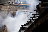 Arezzo: un operaio all'interno dello stabilimento Chimet tra i fumi di vapore acqueo generato dal raffreddamento di metalli fusi. L'azienda recupera metalli preziosi (oro, platino, palladio, iridio, argento) da materiali di scarto come catalizzatori di marmitte, batterie, contatti elettrici di cellulari, computer o materiali di scarto industriale.<br /> <br /> Arezzo: The Chimet company recovers precious metals (gold, platinum, palladium, iridium, silver) from waste materials such as catalysts, mufflers, batteries, electrical contacts to phones, computers or industrial waste materials.