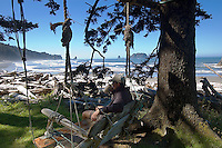 Hiker relaxing and drinking coffee from mug, in driftwood swing at beach camp, Coastal Strip, Olympic National Park, WA.