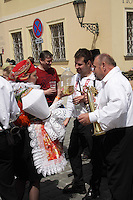Young woman dressed in a typical Moravian costume is serving new wine to the Musicians at the Ride of Kings event in Prague.<br /> <br /> Twelve-year-old Frantisek Libosvar dressed as a girl and with a rose in his mouth leads the royal procession during Ride of the Kings as part of Navalis Celebrations on May 15, 2015 in Prague, Czech Republic. The Navalis Saint John's celebrations take place to commemorate Czech saint and Prague native, Saint John of Nepomuk, patron of all people of the water. <br /> <br /> <br /> The Ride of the Kings takes place during the spring, as a part of the Pentecost traditions . A group of young men ride through a Prague in a ceremonial procession. The ride is headed by chanters, followed by pageboys with unsheathed sabres who guard the King &ndash; a young boy with his face partially covered, holding a rose in his mouth &ndash; and the rest of the royal cavalcade. The King and pageboys are dressed in women&rsquo;s ceremonial costumes, while the other riders are dressed as men. The entourage rides on decorated horses, stopping to chant short rhymes that comment humorously on the character and conduct of spectators. The chanters receive donations for their performance, placed either in a money box or directly into the riders&rsquo; boots. The King&rsquo;s retinue returns home after a few hours of riding, and celebrates in the evening at the house of the King with a small feast, music and dancing. The practices and responsibilities of the Ride of the Kings are transmitted from generation to generation. The traditional paper decorations for the horses and the ceremonial costumes, in particular, are made by women and girls familiar with the processes, colour patterns and shapes specific to each village.